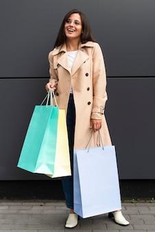 Vue de face d'une femme souriante tenant beaucoup de sacs à provisions à l'extérieur