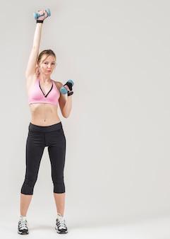 Vue de face d'une femme sportive exerçant avec des poids