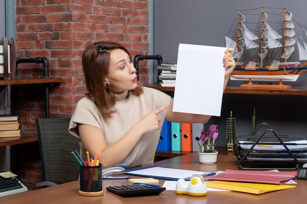 Vue de face femme surprise en pointant sur des papiers assis au mur