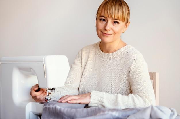 Vue de face femme tailleur à l'aide de machine à coudre
