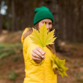 Vue de face femme tenant une feuille jaune