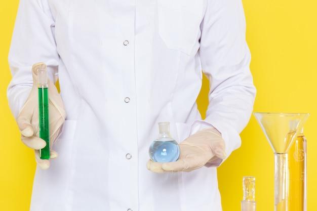 Vue de face de la femme tenant des flacons avec des solutions chimiques
