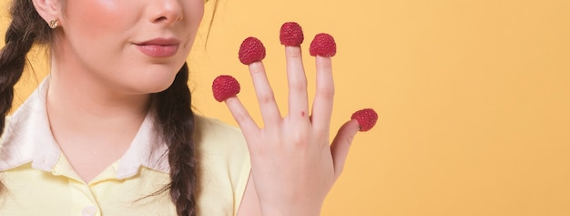 Vue de face de femme tenant la main avec des framboises sur le doigt