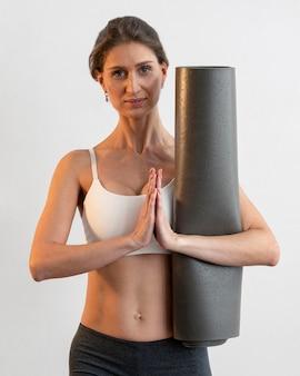 Vue de face de la femme tenant un tapis de yoga tout en faisant une pose