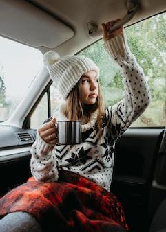 Vue de face femme tenant une tasse de café dans la voiture
