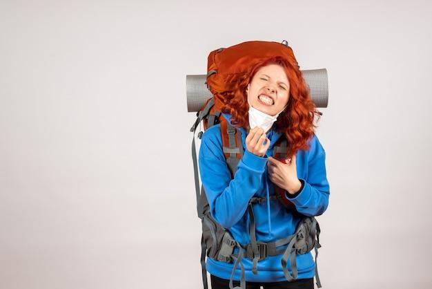 Vue de face femme touriste en masque avec sac à dos fatigué
