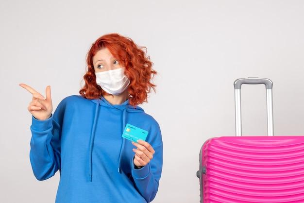 Vue de face femme touriste en masque tenant une carte bancaire