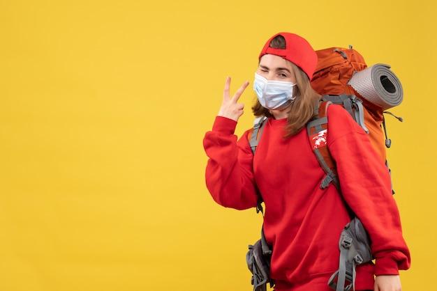 Vue de face femme touriste avec sac à dos touristique et masque oeil clignotant faisant signe de la victoire