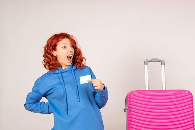 Vue de face femme touriste avec sac rose et tenant une carte bancaire