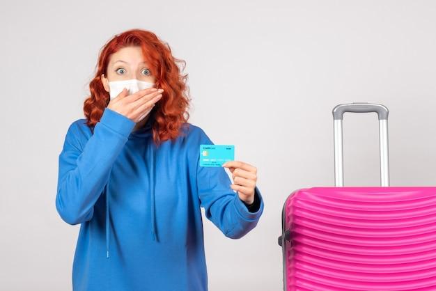 Vue de face femme touriste tenant une carte bancaire en masque