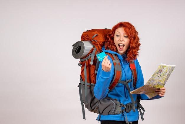 Vue de face de la femme touriste en voyage en montagne avec carte et carte bancaire