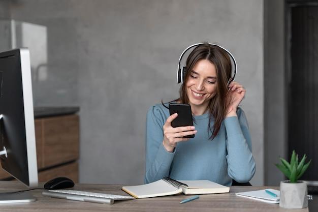 Vue de face de la femme travaillant dans le domaine des médias avec smartphone et casque