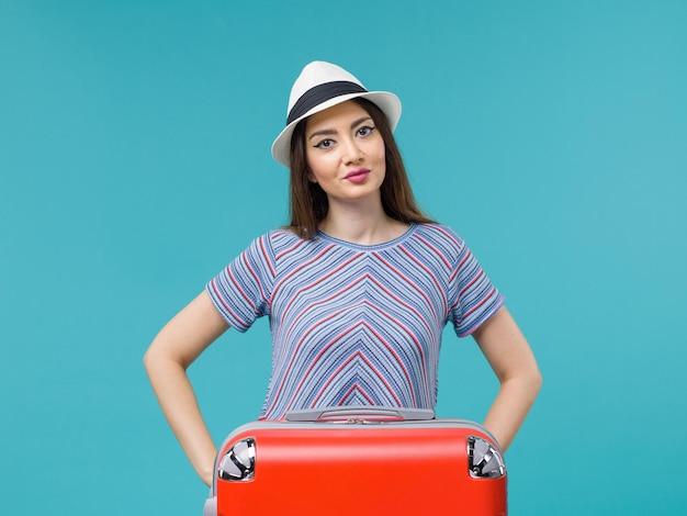 Vue de face femme en vacances avec son sac rouge profitant de son voyage sur le fond bleu voyage voyage vacances femme voyage