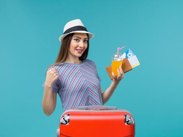 Vue de face femme en vacances avec son sac rouge tenant des billets et du jus sur bureau bleu voyage voyage voyage vacances femme