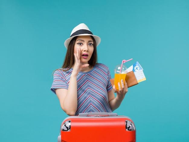 Vue de face femme en vacances avec son sac rouge tenant des billets et du jus sur un fond bleu voyage voyage vacances femme voyage
