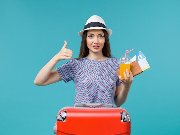 Vue de face femme en vacances avec son sac rouge tenant des billets et du jus sur un fond bleu voyage voyage voyage vacances femme