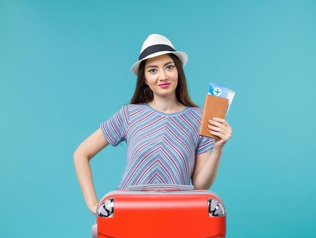 Vue de face femme en vacances avec son sac rouge tenant des billets sur fond bleu billet voyage voyage voyage vacances femme