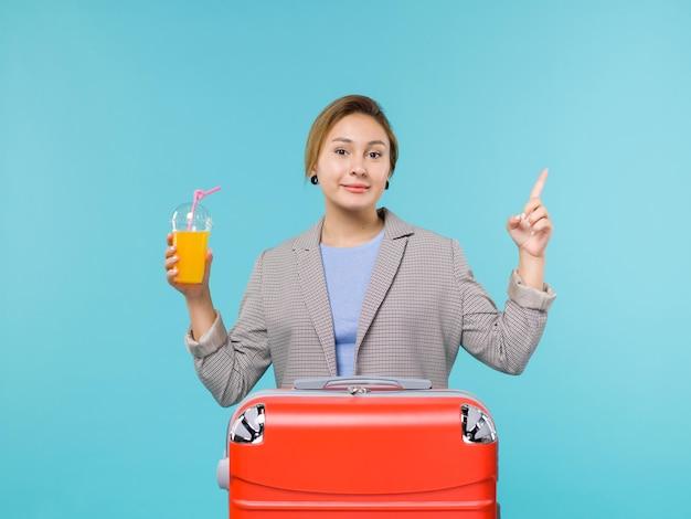 Vue de face femme en vacances avec son sac rouge tenant du jus de fruits frais sur le bureau bleu vacances avion voyage voyage en mer