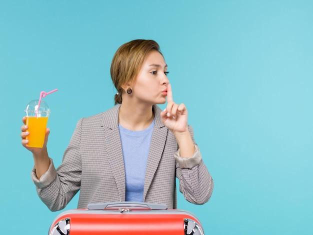 Vue de face femme en vacances avec son sac rouge tenant du jus de fruits frais sur le fond bleu mer vacances avion voyage voyage voyage
