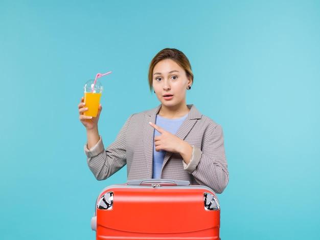 Vue de face femme en vacances avec son sac rouge tenant du jus de fruits frais sur le fond bleu vacances avion voyage mer voyage