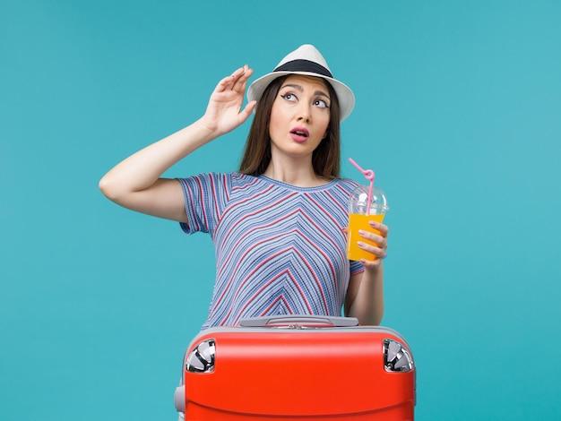 Vue de face femme en vacances avec son sac rouge tenant son jus sur le fond bleu voyage été mer voyage voyage vacances