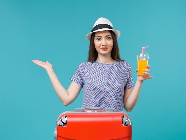 Vue de face femme en vacances avec son sac rouge tenant son jus sur le fond bleu voyage voyage vacances femme voyage