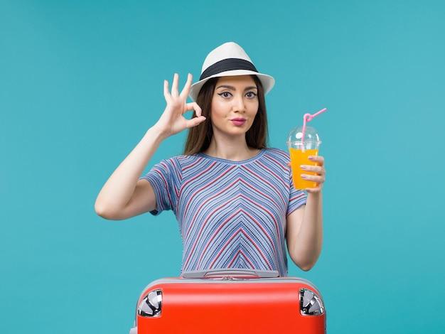 Vue de face femme en vacances avec son sac rouge tenant son jus sur le fond bleu voyage voyage voyage vacances femme