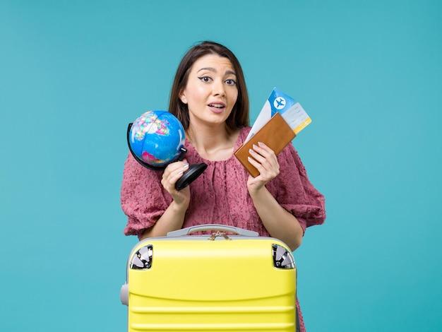Vue de face femme en vacances tenant des billets d'avion et de globe sur le bureau bleu mer vacances femme voyage voyage été
