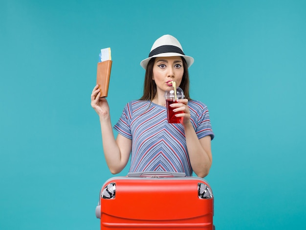 Vue de face femme en vacances tenant des billets et du jus sur le fond bleu voyage voyage été femme avion de mer