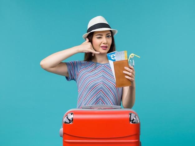 Vue de face femme en vacances tenant des billets sur fond bleu voyage voyage femme mer avion été