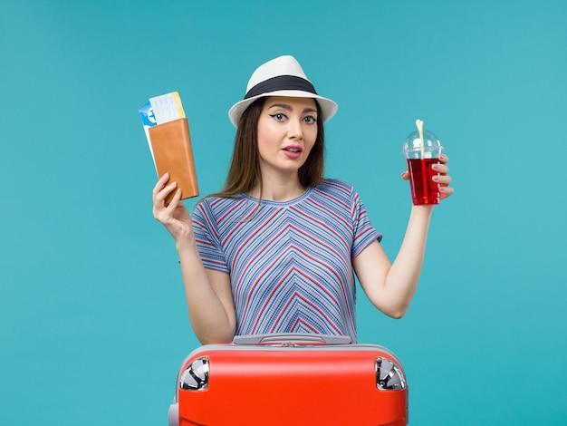 Vue de face femme en vacances tenant des billets et jus rouge sur le fond bleu mer voyage voyage vacances femme