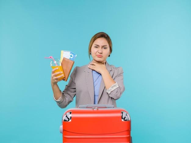 Vue de face femme en vacances tenant une boisson fraîche et des billets sur fond bleu mer vacances voyage voyage