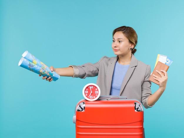 Vue de face femme en vacances tenant la carte et les billets sur un fond bleu avion voyage mer voyage vacances