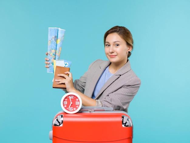 Vue de face femme en vacances tenant la carte et les billets sur fond bleu avion voyage voyage voyage voyage vacances mer