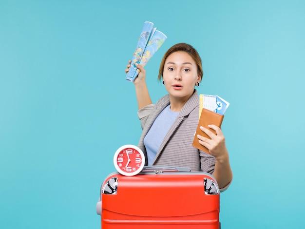 Vue de face femme en vacances tenant la carte et les billets sur fond bleu clair avion voyage mer voyage vacances