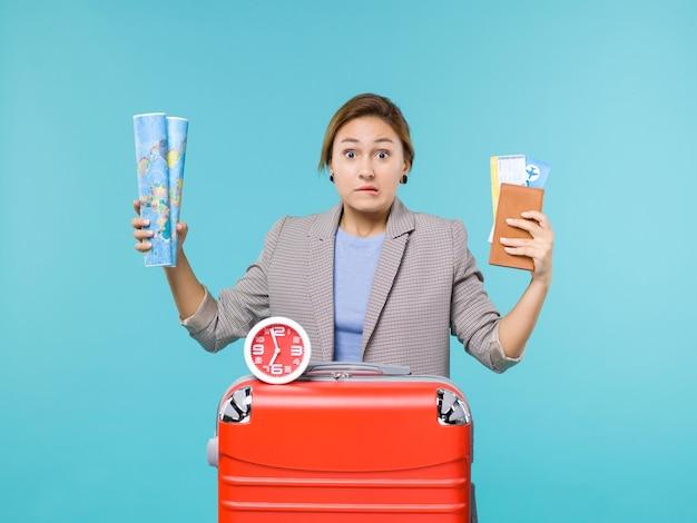 Vue de face femme en vacances tenant la carte et les billets sur fond bleu clair avion voyage voyage voyage vacances mer voyage