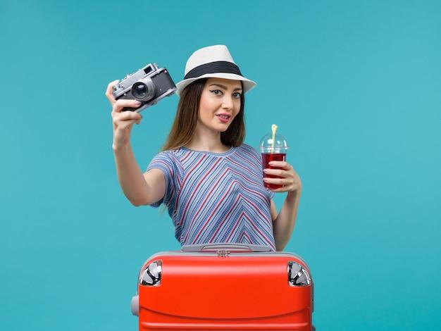 Vue de face femme en vacances tenant du jus avec appareil photo sur le fond bleu mer voyage en avion voyage d'été