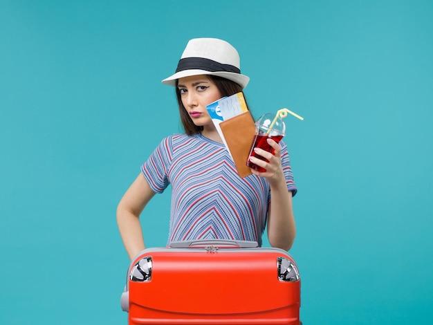 Vue de face femme en vacances tenant du jus avec des billets sur fond bleu femme mer voyage été voyage en avion