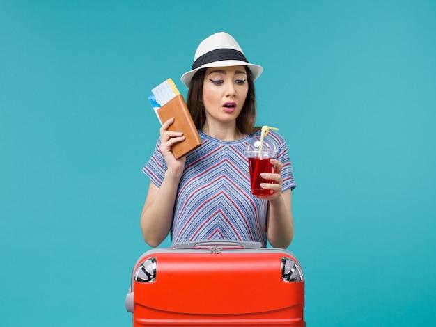 Vue de face femme en vacances tenant du jus avec des billets sur le fond bleu mer voyage été voyage avion femme