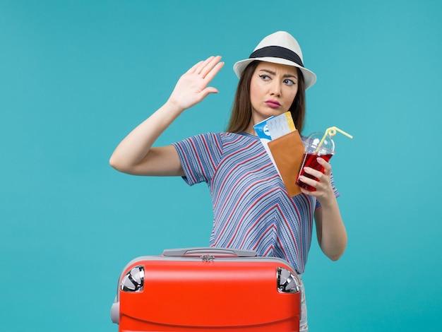 Vue de face femme en vacances tenant du jus avec des billets sur le fond bleu voyage voyage en avion été mer femme