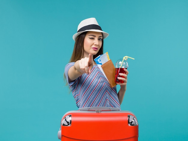 Vue de face femme en vacances tenant du jus avec des billets sur le fond bleu voyage voyage avion été mer femme
