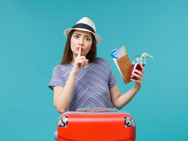 Vue de face femme en vacances tenant du jus avec des billets sur le fond bleu voyage voyage femme été avion de mer
