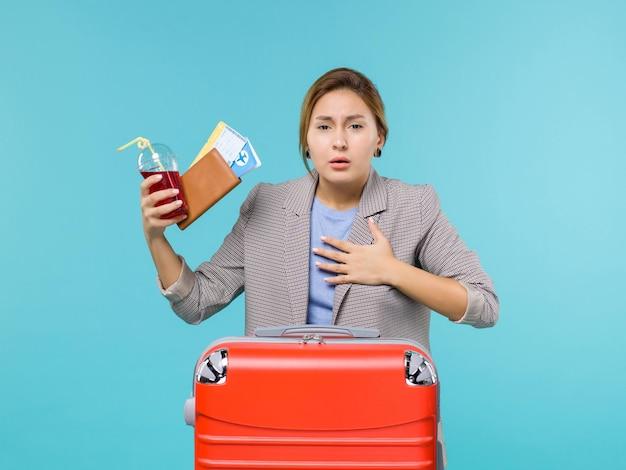 Vue de face femme en vacances tenant du jus avec des billets tousser sur le fond bleu voyage voyage vacances voyage avion de mer
