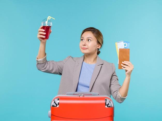 Vue de face femme en vacances tenant du jus de cerise frais et des billets sur le fond bleu voyage voyage avion vacances voyage