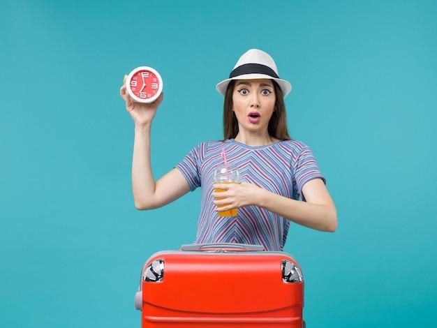 Vue de face femme en vacances tenant du jus et de l'horloge sur fond bleu clair voyage vacances mer voyage voyage