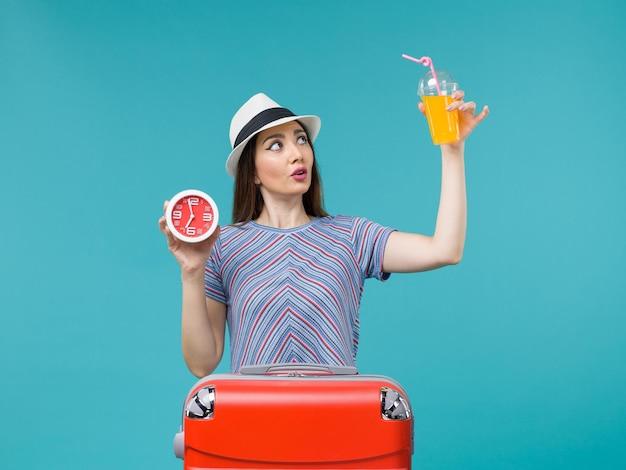 Vue de face femme en vacances tenant du jus et de l'horloge sur fond bleu voyage vacances mer voyage voyage femme