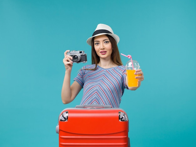 Vue de face femme en vacances tenant le jus et la caméra sur le fond bleu clair voyage voyage été voyage vacances mer