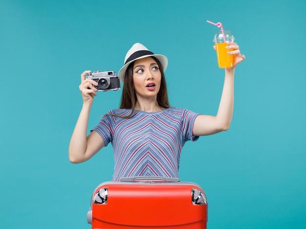 Vue de face femme en vacances tenant le jus et la caméra sur le fond bleu mer voyage voyage été voyage vacances