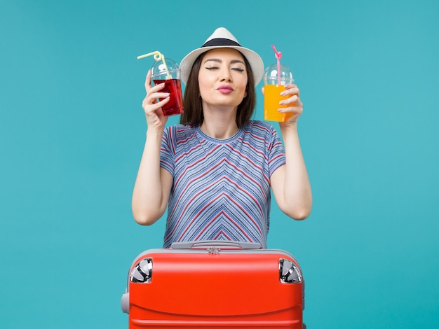 Vue de face femme en vacances tenant des jus de fruits frais sur fond bleu mer voyage voyage avion été