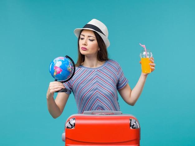 Vue de face femme en vacances tenant jus et globe sur le fond bleu mer voyage vacances été voyage voyage